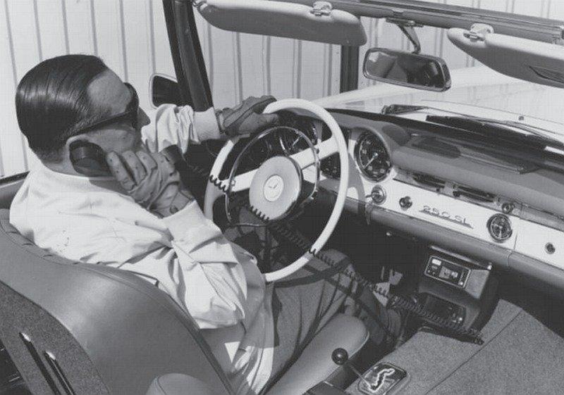 Blick von oben in die Fahrerkabine eines Cabrios. Ein Mann in Anzughose und langärmeligem Hemd telefoniert mit einem fest im Auto eingebauten Telefon.