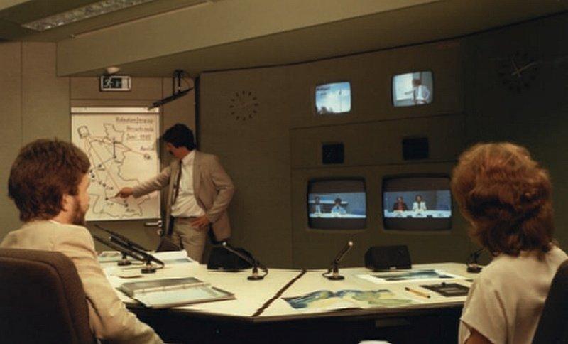 Blick in einen Konferenzraum. Auf dem Tisch sind Mikrofone und Lautsprecher montiert, an der Wand dahinter mehrere Bildschirme.