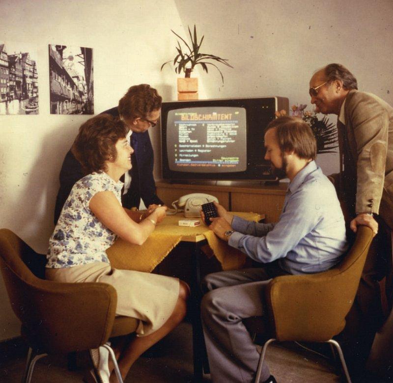 Vier Personen sind vor einem Fernseher versammelt, auf dem der Bildschirmtext offen ist. Ein Mann hält die Fernbedienung in der Hand und erklärt die Bedienung, die anderen schauen interessiert.