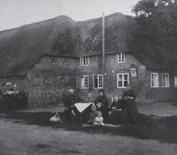 Vor einem Haus sitzt eine Gruppe von sieben Personen