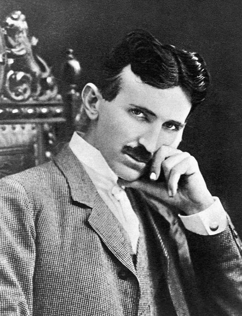 Ein dunkelhaariger Mann mit welligem Haar und Schnurrbart, bekleidet mit einem weißen Hemd und hellen Anzug, stützt den Kopf in die Hand und schaut fast kokett in die Kamera.