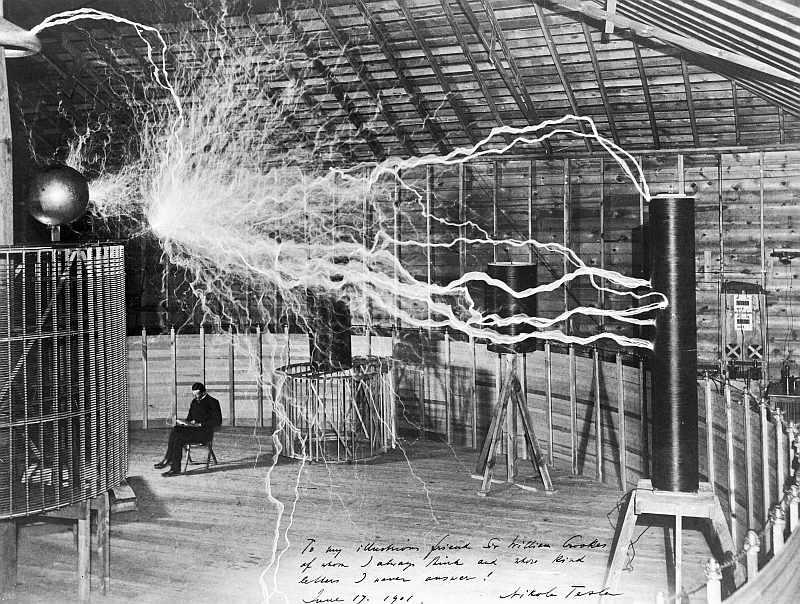 Blick in ein Labor. Ein Mann sitzt lesend auf einem Stuhl, über ihm findet eine heftige elektrische Entladung statt, die er keines Blickes würdigt.