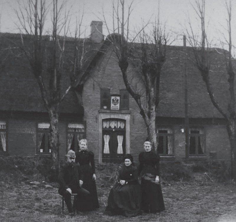 Ein älterer Mann und eine ältere Frau sitzen auf Stühlen vor einem Haus. Neben ihnen stehen zwei jüngere Frauen.