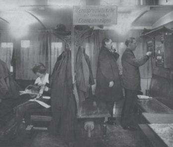 Zwei Männer stehen im Zugabteil vor einem Münzfernsprecher. Einer telefoniert bereits, einer wählt.